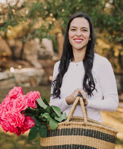Dr. Alejandra Carrasco holding basket of flowers