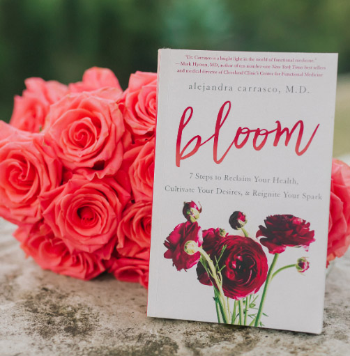 Bloom book cover in front of flowers